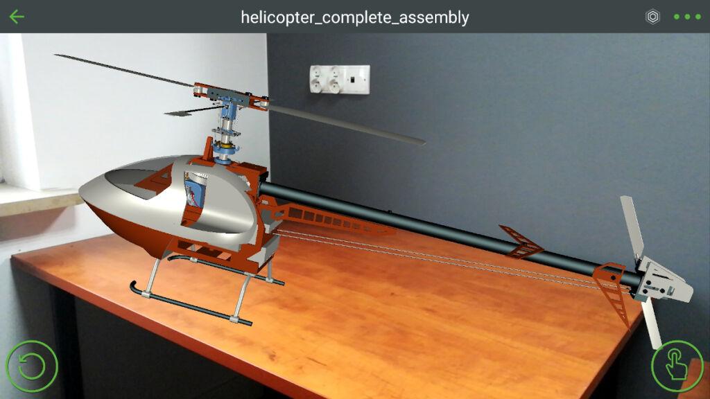 Grafika przedstawiająca model wyświetlony rzeczywistości rozszerzonej na płaskiej powierzchni stołu.